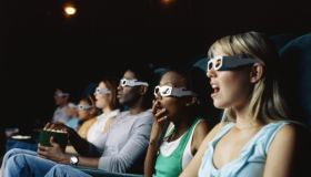 Large group of people watching movie in a movie theatre wearing 3D glasses