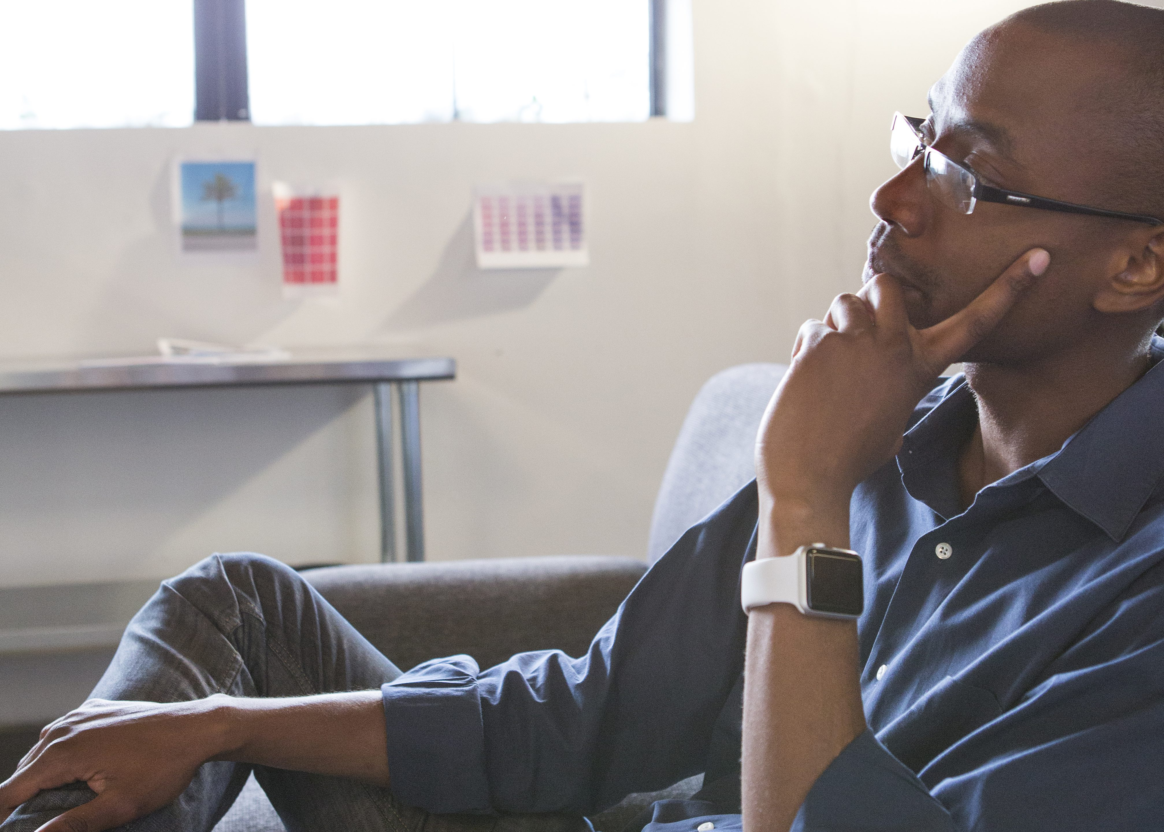 Mixed race businessman thinking in office