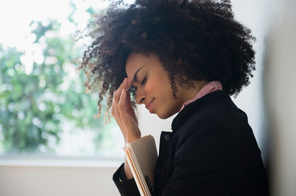 Stressed mixed race businesswoman rubbing her forehead