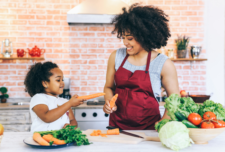Mother making salad with her daughter in Isolation at home during virus. Kids cooking at home