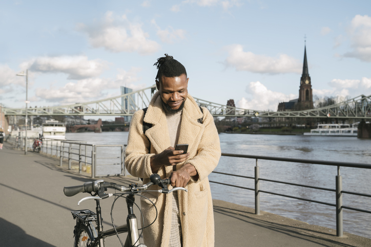 Stylish man with a bicycle using smartphone on riverbank, Frankfurt, Germany